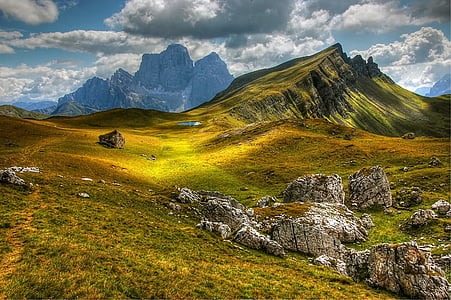 green covered grass mountain under white clouds