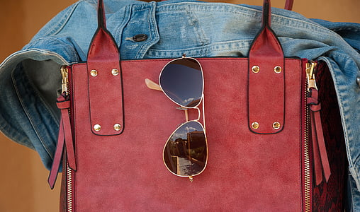 black sunglasses hanging on red leather bag