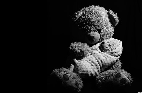 grayscale photography of brown bear plush toy carrying baby plush toy