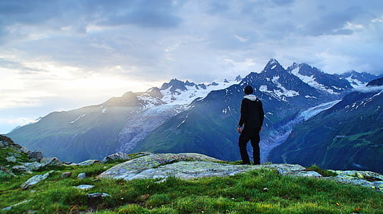 man standing on cliff fronting mountain covered with snow