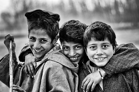 grayscale photo of three boys smiling
