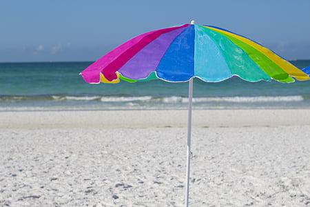 rainbow-colored umbrella on seashore