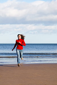 woman wearing red long-sleeved shirt running on beach