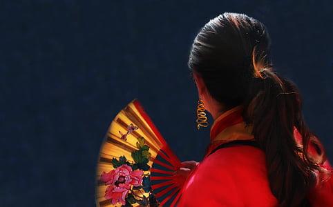 woman' holding floral folding hand fan