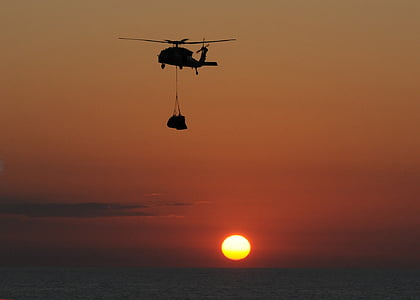 helicopter carrying cargo over body of water during golden hour