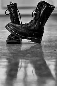 pair of black Doc Martens combat boots on gray surface