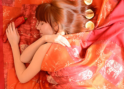 closeup photography of woman sleep on orange and multicolored floral bed comforter