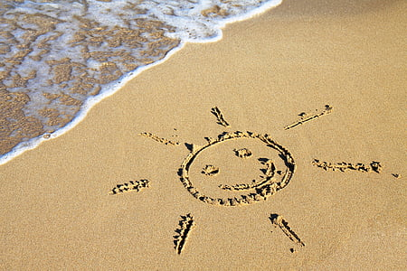 photo of sun illustration on sand near body of water during daytime