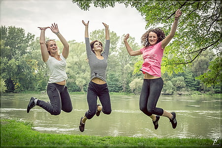 three woman jumping near river