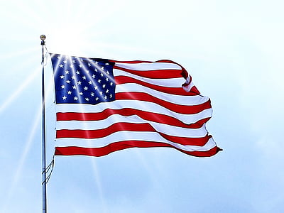 flag of U.S.A hanged on gray metal pole at daytime