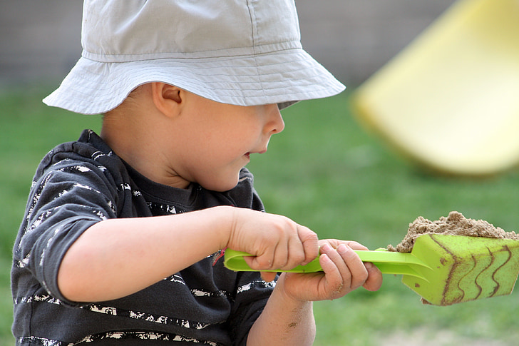 toddler with green plastic sand scoop