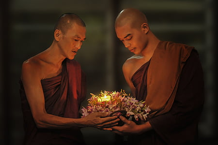 two monks carrying flowers with candle