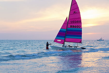 person beside white sail boat