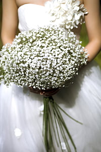 photo of woman wearing white wedding dress holding white petaled flowers bouquet