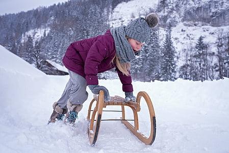 girl holding brown wooden sled