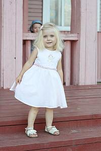 girl wearing white dress standing on wooden ladder