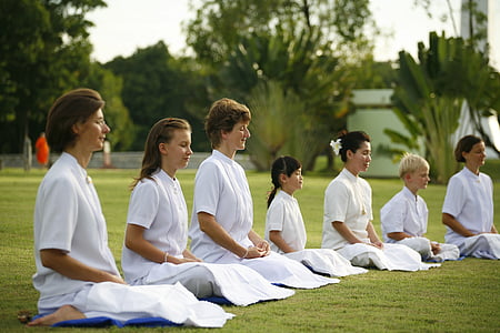 people sitting on grass while meditating