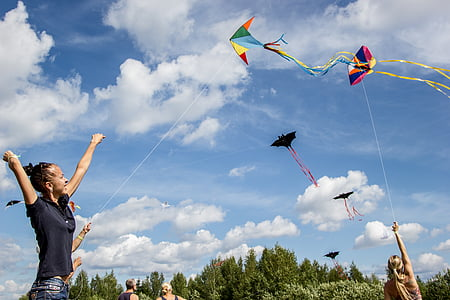 woman holding playing paper kite under cloudy blue sky during daytime
