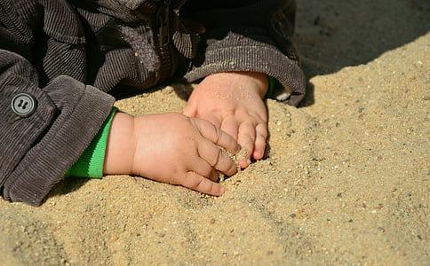 closeup photo of kid wearing black corduroy jacket holding brown sand
