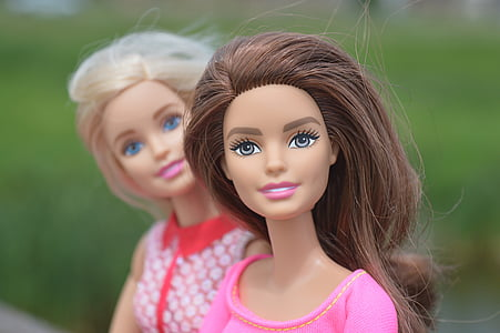 macro photography of two Barbie dolls