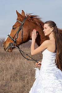 woman in tube dress holding brown horse