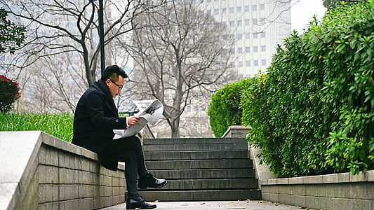 man wearing black coat while reading newspaper