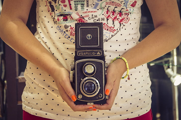 woman holding black Yashico-A reflex camera