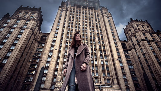 HRD photography of woman standing in front of high-rise building during daytime