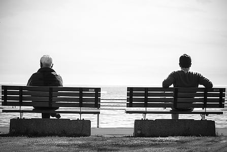 grayscale photography of men sitting on bench