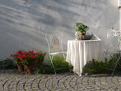 white wrought iron 3-piece patio set near red petaled flowers