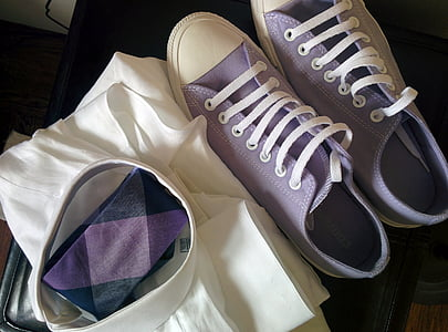 purple low-top sneakers beside white textile