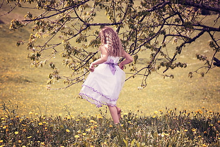 girl in pink playing on grass field