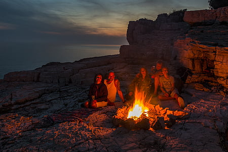 two men and three women sitting on front of campfire