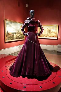 mannequin wearing burgundy velvet gown on display