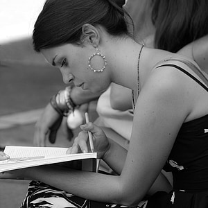 grayscale photo of woman with white book