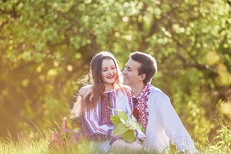 woman and man sitting on green grass field during daytime