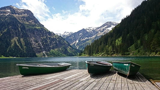 three green canoe boats on brown wooden dock beside body of water near mountains