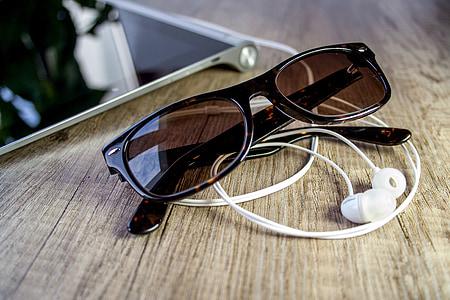 Wayfarer sunglasses near canalbuds on wooden surface
