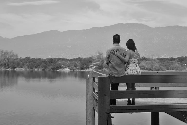 couple sitting on fence near body of water