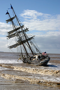 white and brown sail boat on sea shore