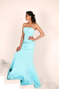 woman in blue sweetheart-neckline dress standing on the stairs