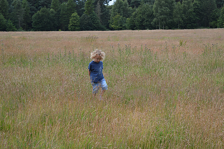 toddler standing in the middle of grass