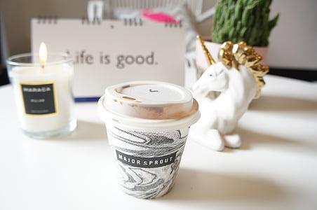 white and black plastic cup near white unicorn ceramic figurine
