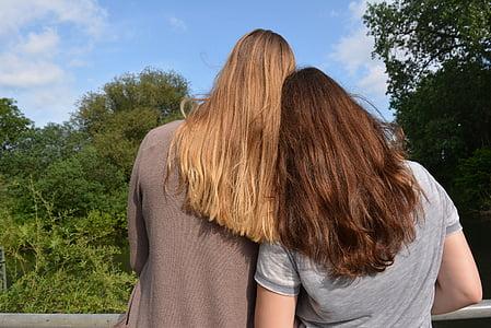 woman wearing gray shirt standing beside woman wearing brown jacket