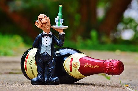 butler figurine beside wine bottle