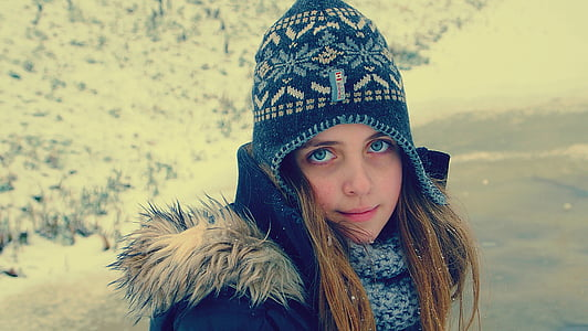 girl wearing blue hat and black coat at daytime
