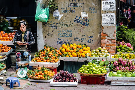 woman wearing black track jacket standing in front of weighing scale and fruit stand at daytime