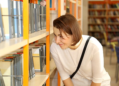 woman wearing white shirt looking through books on shelves
