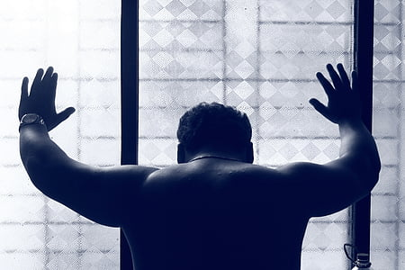 topless man leaning on wall glass wall