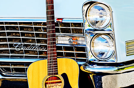 brown acoustic guitar leaning on white Cadillac car